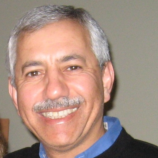 Smiling man with mustache, wearing a blue collared shirt below a black sweater