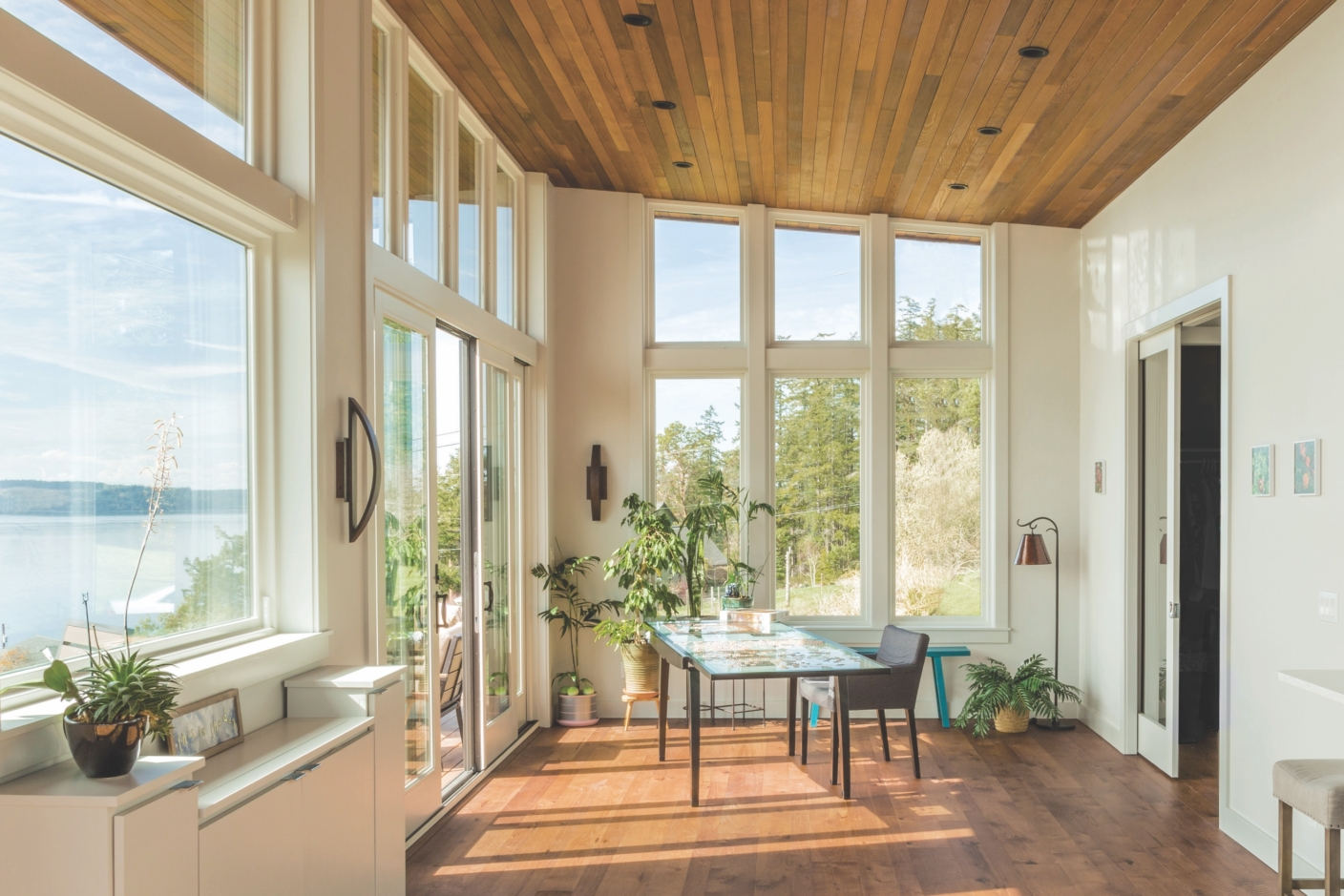 Bloom House interior with large windows onto natural landscape, with wood-paneled floors and ceiling
