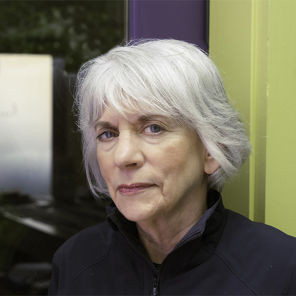 Gray-haired woman in black jacket in front of tri-color background