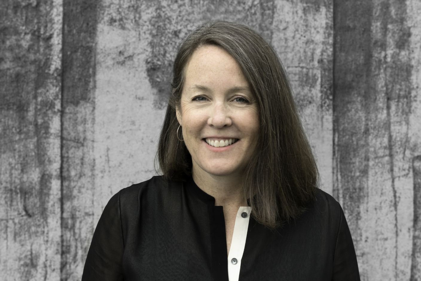 Smiling photo of woman with dark-with-gray hair parted on her right-hand side, wearing a black shirt with white lapel in front of gray, abstracted background