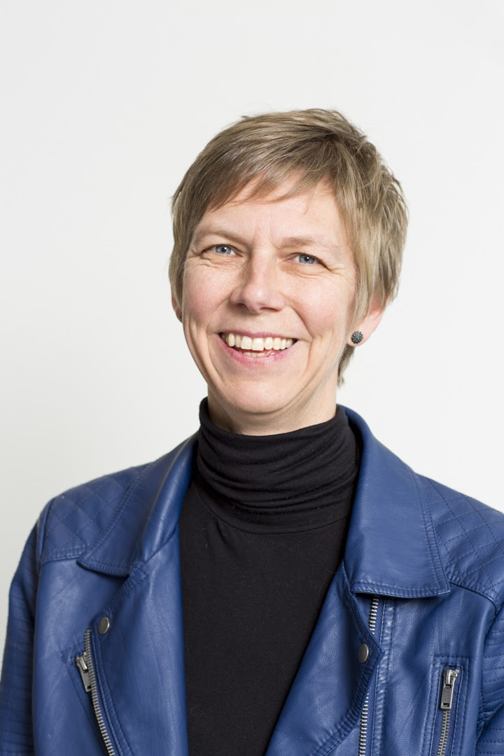 Smiling studio portrait of woman with short light-brown hair, wearing a blue jacket over a black sweater