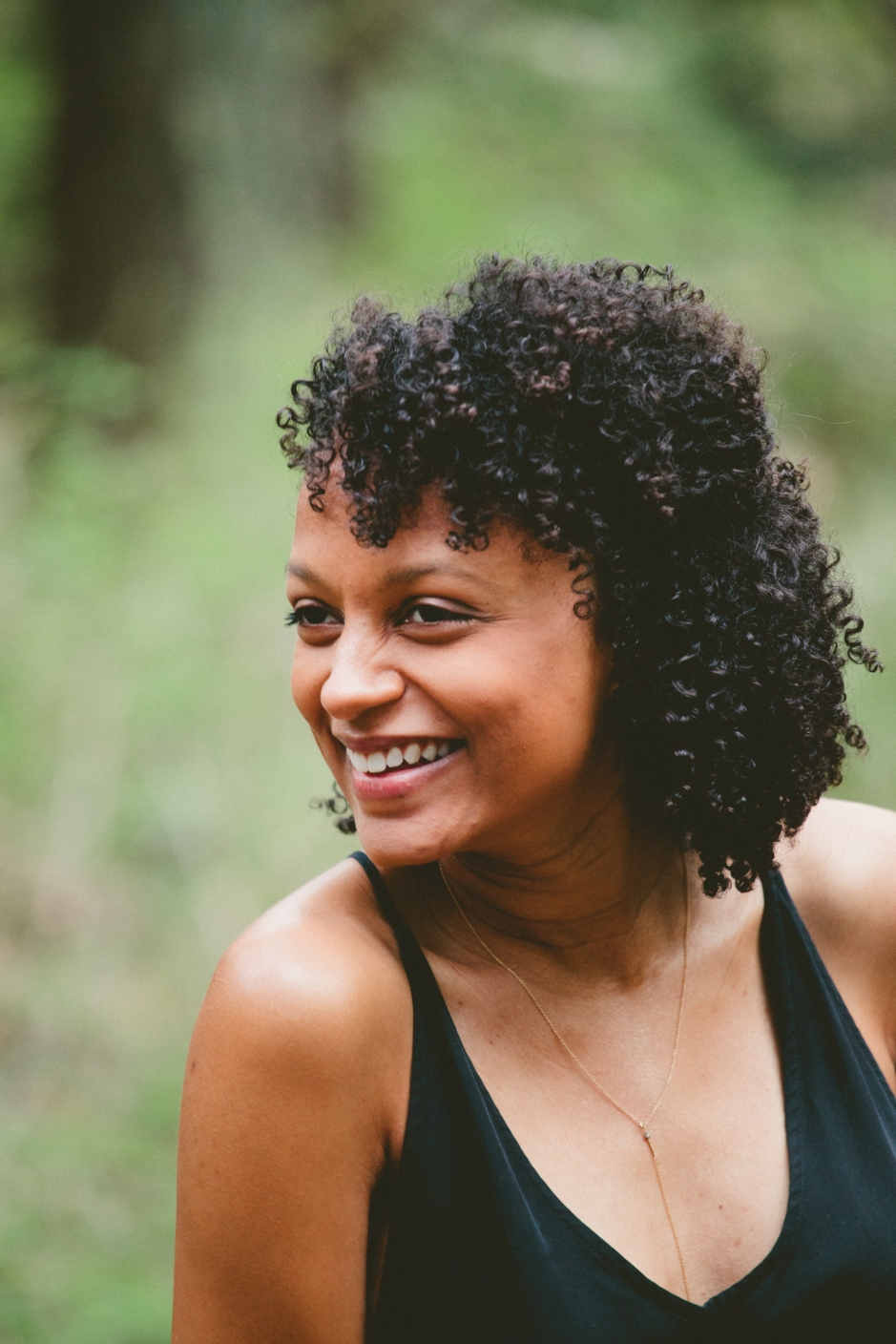 Woman in black, sleeveless top and curly hair, turning her head and smiling, in front of unfocused nature background