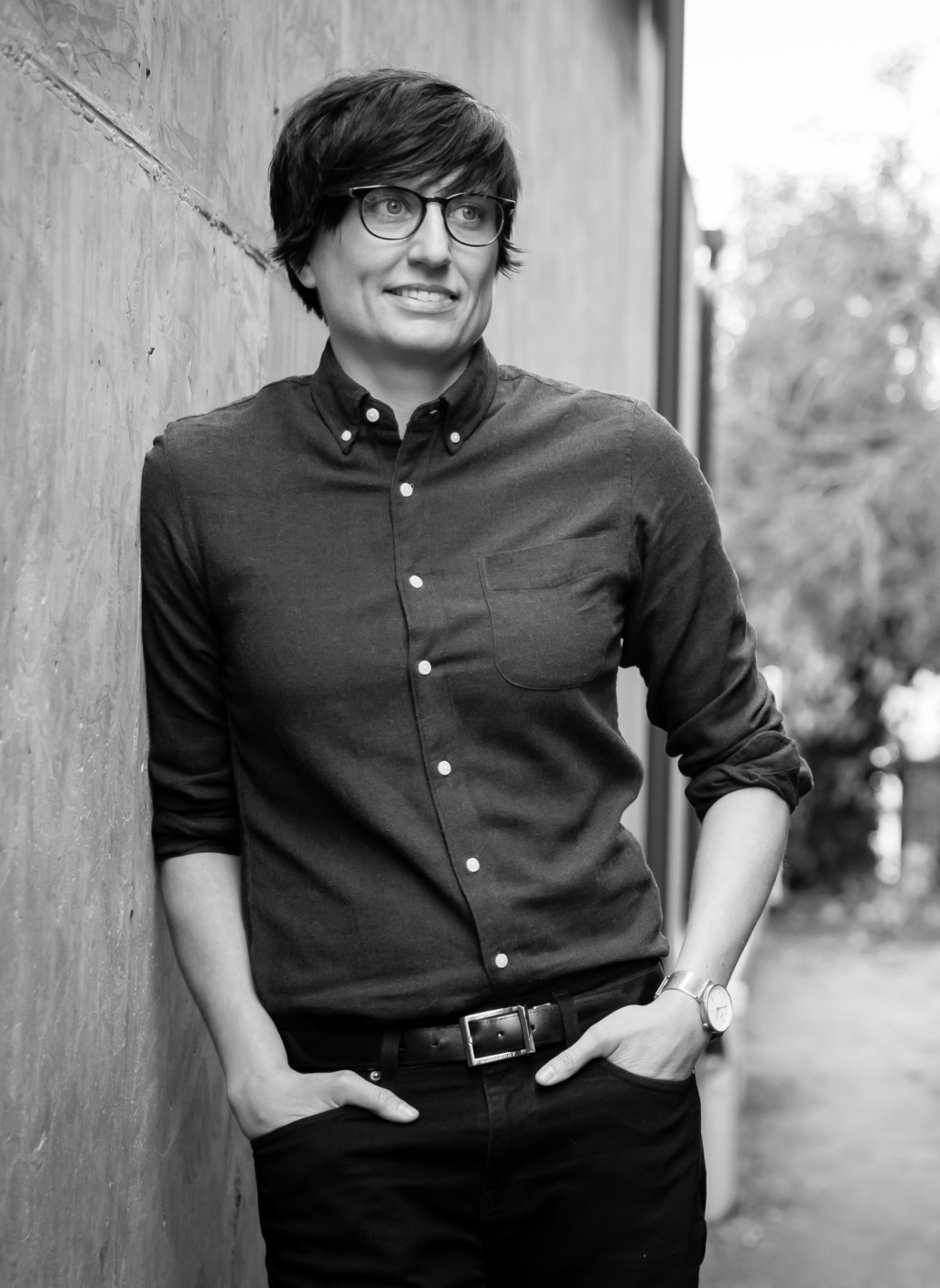 Black-and-white portrait of woman with dark, short hair, bangs, and glasses, in a dark, collared shirt and hands in pockets, leaning against a concrete wall in front of trees.