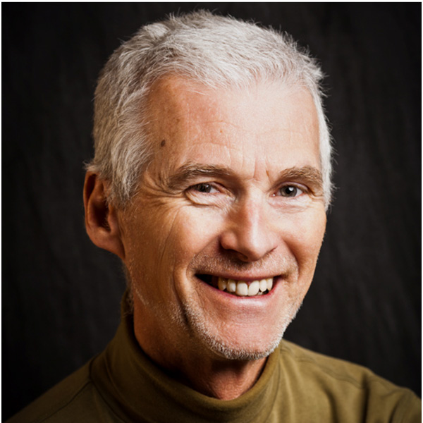 Smiling grey-haired man in green/brown sweater, in front of black background