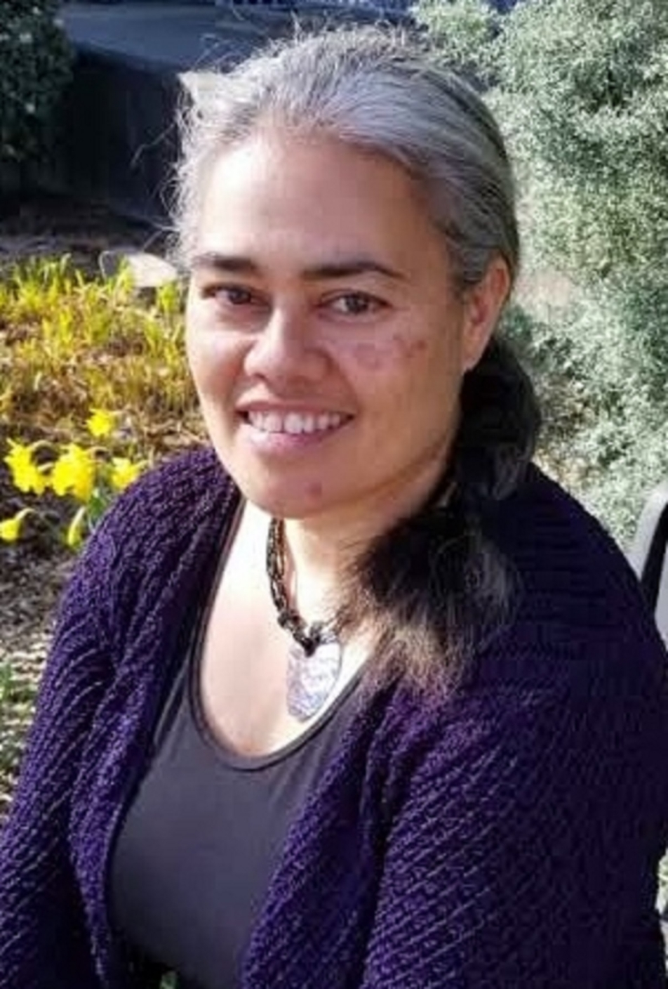 Smiling person with ponytail, wearing a necklace and purple sweater over grey shirt