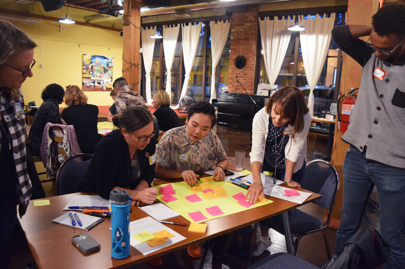 Participants around a table work together on a collaborative sticky-note exercise